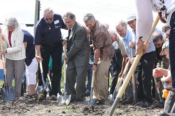 Hundreds turned out for MCC BC's groundbreaking celebrations on the site of the new MCC Centre in Abbotsford, B.C. Siegfried Bartel, 97, long-serving former MCC BC board chair (centre), and his sons Reinhard (left) and Martin (right) were among those who dug in. Bartel also offered a prayer of blessing for the new project.