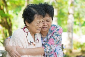 Candid shot of an Asian mature woman hugs and consoling her cryi