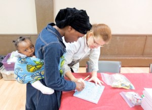 Karen Cornelius demonstrates techniques to a mother.
