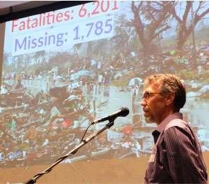 Board chair Len Bloch addresses MCC B.C.'s annual meeting, as slides of Philippines typhoon Haiyan play behind him. British Columbians contributed more than a half-million dollars for MCC relief efforts following that disaster. Photos: Sophie Tiessen-eigbike