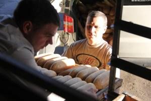 Vlad Makhovskiy (right) with Dmitriy Lichiman (left), another volunteer, prepare bread for distribution to Donetsk and Lugansk.