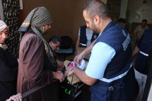 A DFATD-funded project with MCC's partner organization Middle East Council of Churches (MECC) provides non-food items for internally displaced people and vulnerable host communities in Syria's Daraa Governorate. A MECC staff person shows the contents of an aid kit to a recipient who was randomly selected to give her opinion about the items being distributed. Names are not used for security reasons. (MECC photo/Jalal Al-Eid)