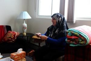 Fatoum Al Kurdi receives an MCC comforter at her family's new apartment in Winnipeg, Manitoba. MCC photo by Emily Loewen.