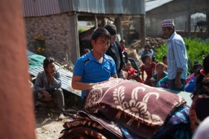 Jiwan Lama (volunteer) helps distribute winter supplies during a distribution done through MCC's partner, Sansthagat Bikas Sanjal (Sanjal) in the village of Bhasbase, Nepal. The distribution provided materials to about 30 households in Dhading District, where homes were destroyed or heavily damaged by the April 25, 2015 earthquake. Sanjal operates through a network of local community based organizations. MCC has worked alongside Sanjal in the districts of Surkhet, Dhading, Okhaldunga and Banke districts on a variety of projects, such as HIV/AIDS prevention, food security, rural education, peacebuilding and disaster response. MCC photo by Matthew Sawatzky