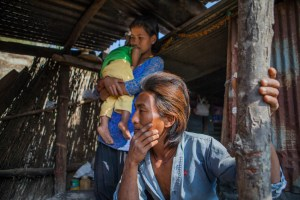 Sudarshan Chepang (22), Jamuna Chepang (18), baby boy Jibesh Chepang (16 months) in their temporary shelter in the village of Bhasebhase, in the Dhading District of Nepal. Their home was destroyed by an earthquake on April 25, 2015. MCC, through its partner, Sansthagat Bikas Sanjal (Sanjal), delivered winter supplies to Bhasbhase in December, 2015. Sanjal operates through a network of local community based organizations. MCC has worked alongside Sanjal in the districts of Surkhet, Dhading, Okhaldunga and Banke on a variety of projects, such as HIV/AIDS prevention, food security, rural education, peacebuilding and disaster response. MCC photo by Matthew Sawatzky