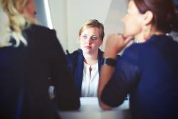 A blonde woman being interviewed in an office by two other women