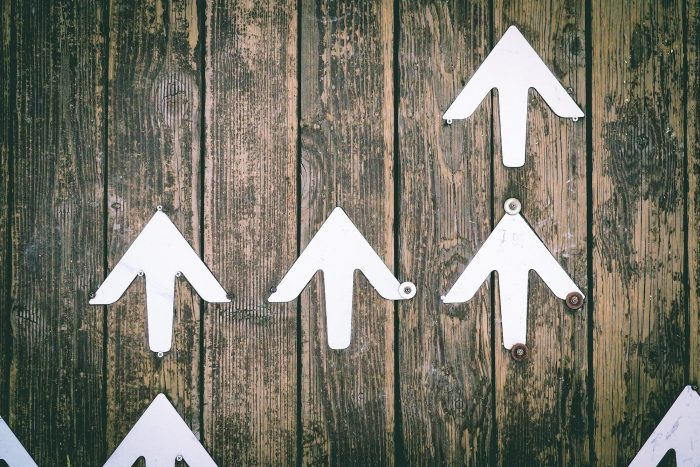 white-painted arrows screwed to wooden boards, representing opportunities for career advancement as part of the seven winning ways to retain top talent