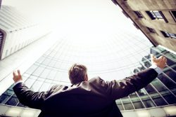 man in a suit from behind holding up his arms in celebration, looking up at office building skyscrapers