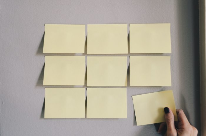 hand placing the last of a series of nine sticky notes, to be used for a team building activity