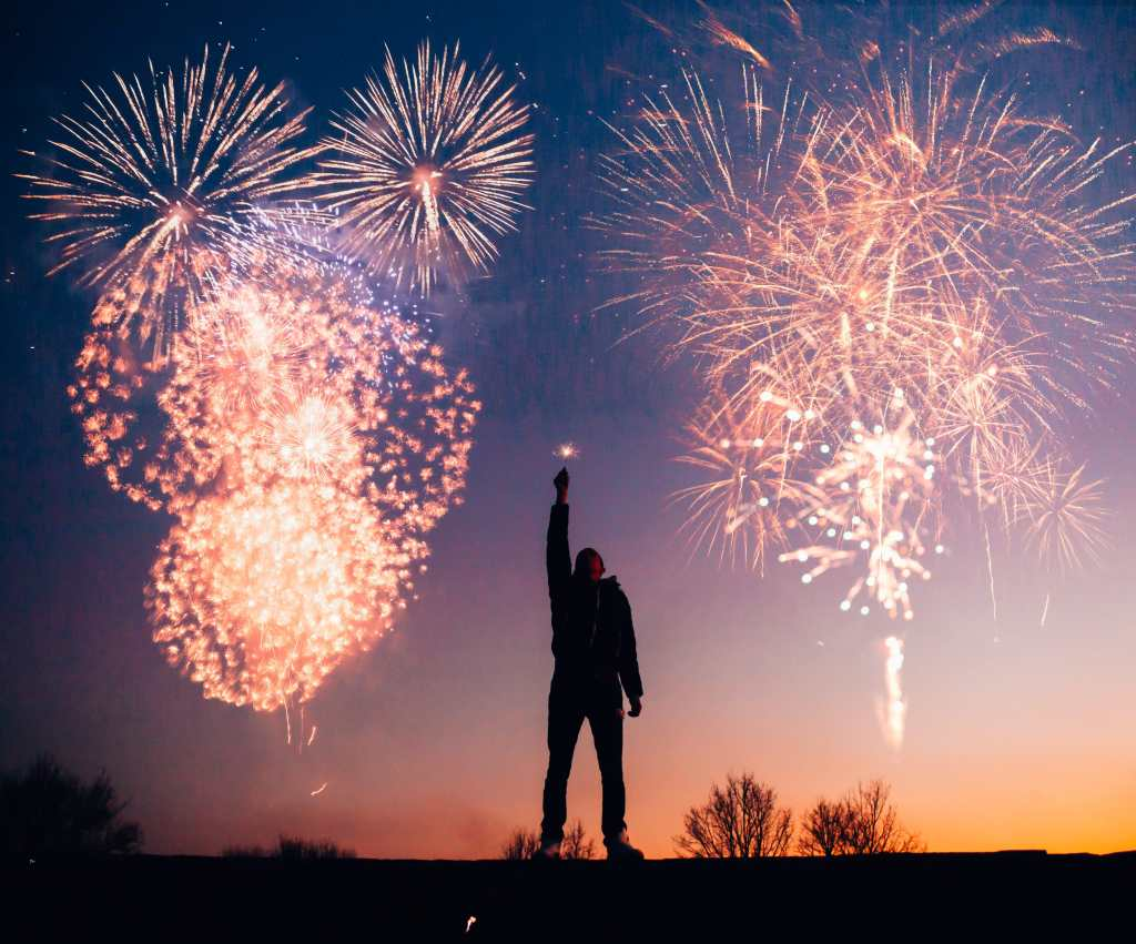Man holding sparkler above his head with fireworks in background