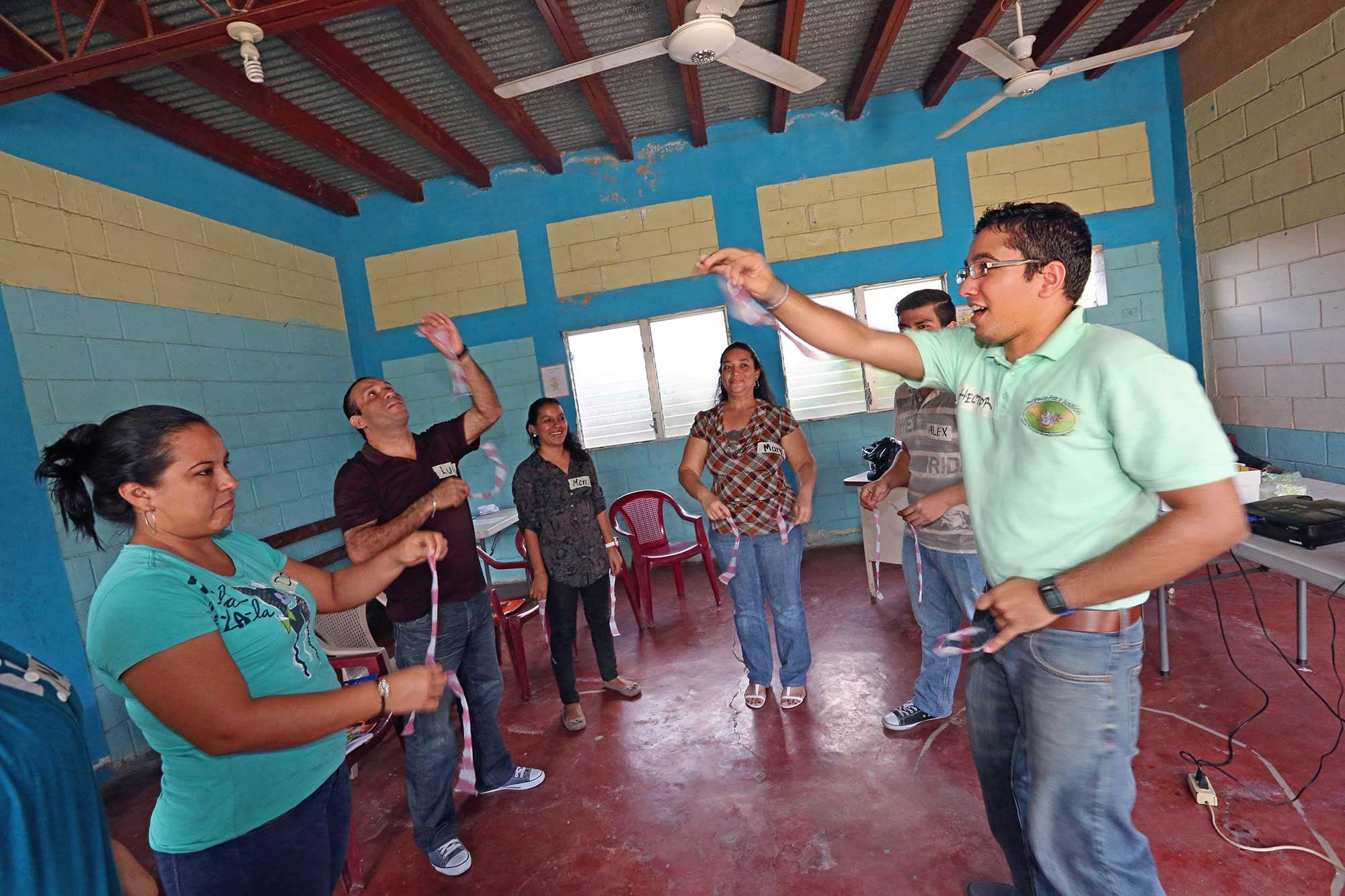 A group standing in a circle throw thin strips of plastic in the air.