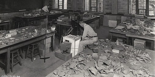 Thomas M.N. Lewis preparing a photographic plate for the publication on the excavations in the Norris Reservoir Basin, January–July 1934. In the upper left is William S. Webb who was supervising archaeologist for the TVA. Excavated artifacts cover the tables in the lab