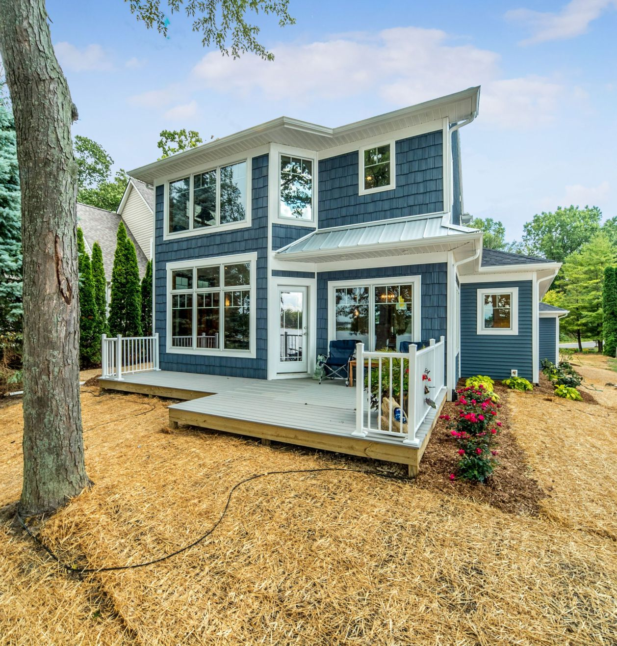 Blue shake two story home with small deck