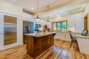 White cabinet kitchen with granite counters and wood island