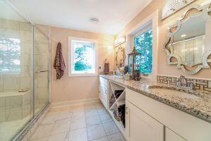 White vanity cabinets opposite glass shower