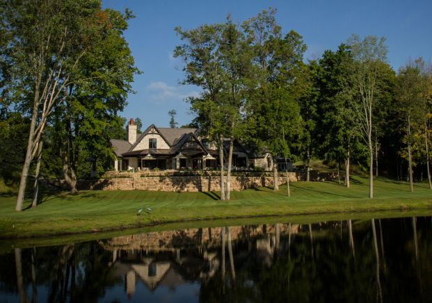 Large stone home set in the trees overlooking a pond