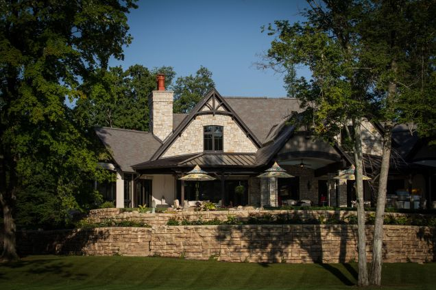 Stone retaining wall anchors large stone house flanked by trees
