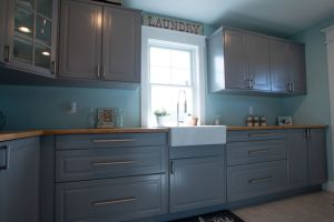 Grey laundry room cabinets with farmhouse sink