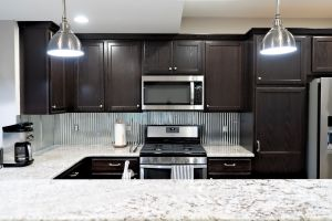 Dark cabinets with corrugated metal backsplach