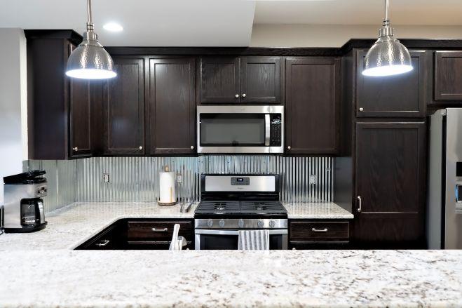 Dark cabinets with corrugated metal backsplach