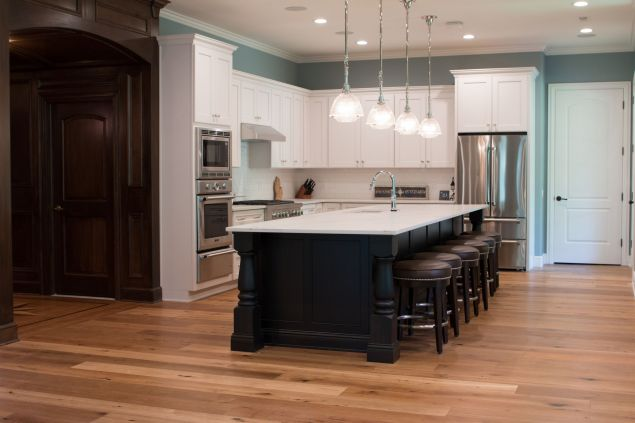 Large wood island with white marble top in kitchen with white cabinets