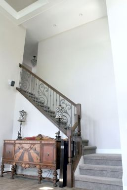 Staircase with wood railing and decorative iron ballusters