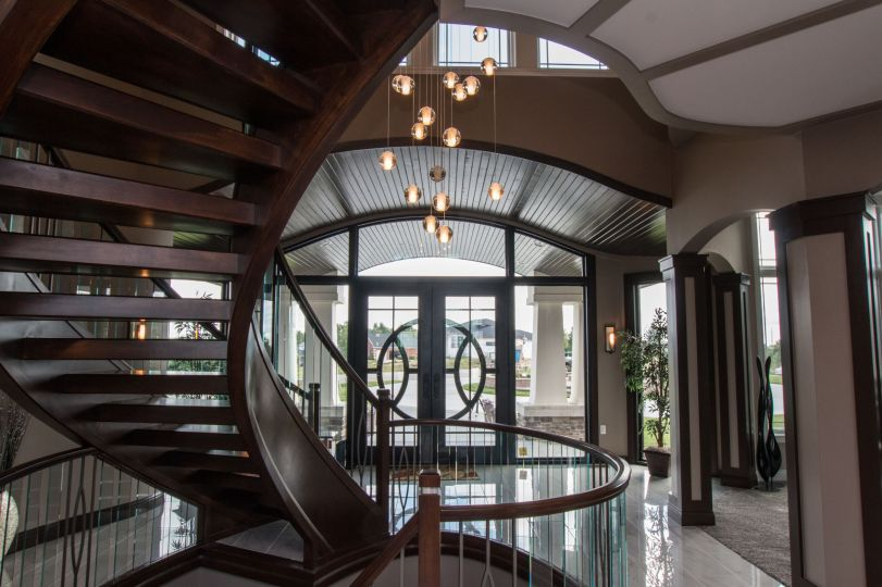 Looking through the entry towards the front door with winding staircase