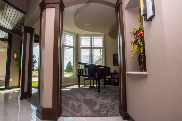 A grand piano framed between two custom wood trimmed pillars