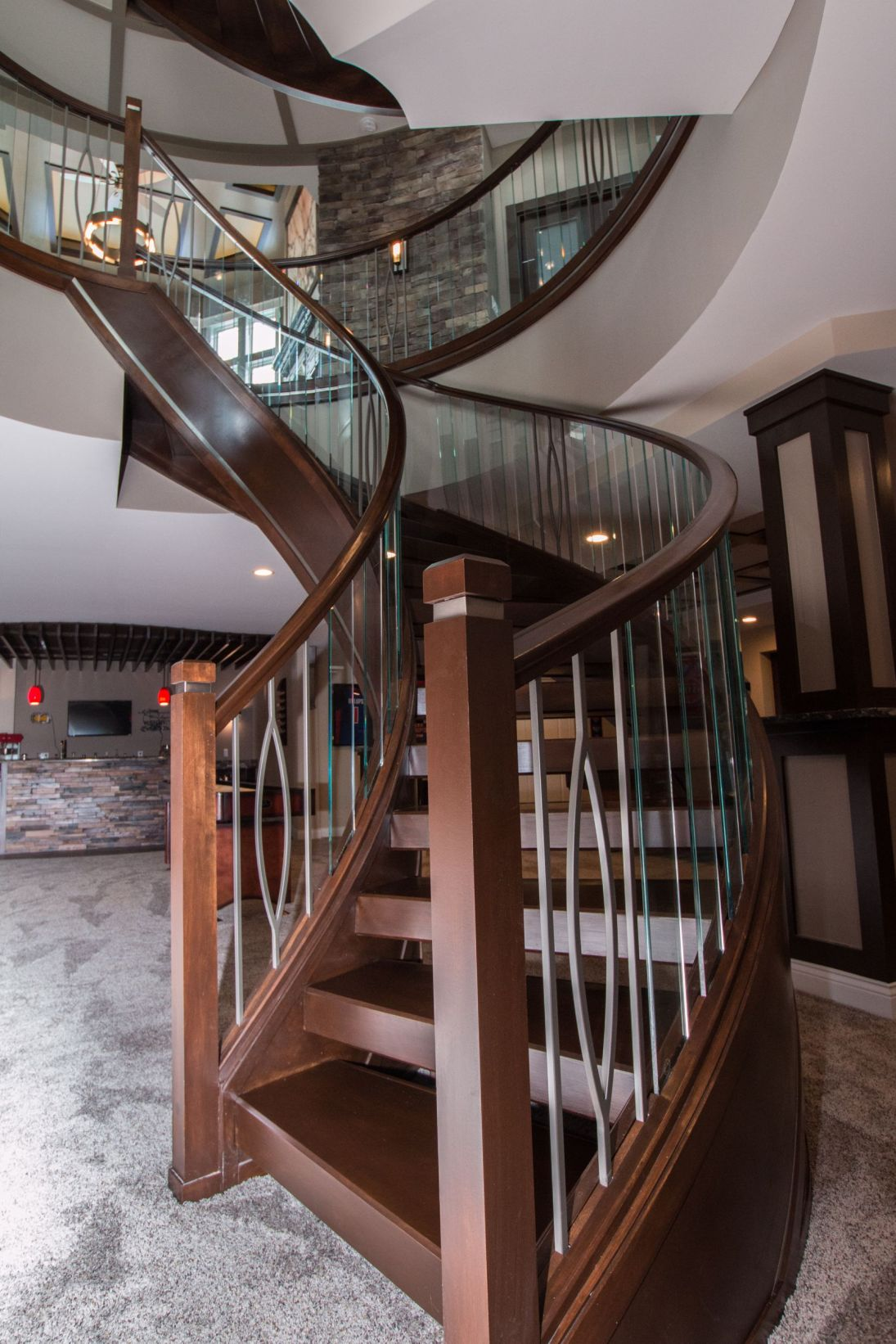 Wood newel post with a mix of glass and metal balusters wind around a curved wood staircase