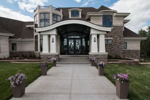 Entry of home with curved porch roof and large tapered columns