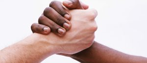 photo of a Black individual's hand entertwined with a White individuals hand representing the BIPOC therapy fund at Montgomery County Counseling Center.