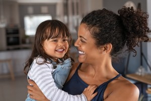 happy adult woman hugs her child. She got adult therapy in Rockville, MD with a therapist at Montgomery County Counseling Center