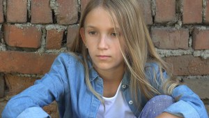 teen girl sits on the floor against a wall looking upset. She gets a DBT and joins an online DBT skills group in maryland or an online DBT skills group in Virginia or an online DBT skills group in Washington DC