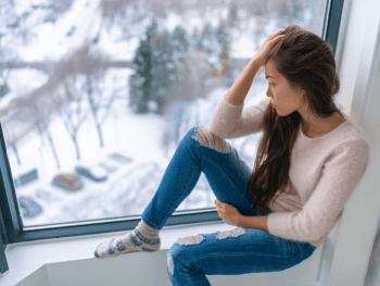 woman staring out the window looking sad during the winter
