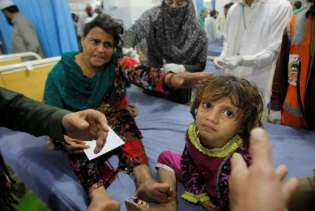 WOMAN AND DAUGHTER WAIT FOR TREATMENT IN PESHAWAR, PAKISTAN HOSPITAL