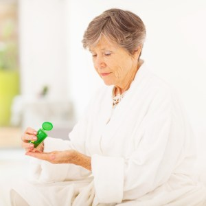 An older woman is shown taking medication