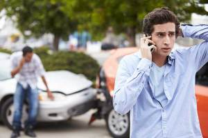 Driver taking on the phone after a car accident.