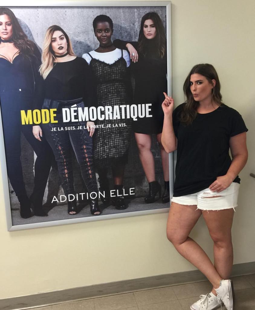 Gabrielle Threlfall devant une publicité d'elle-même pour Addition Elle