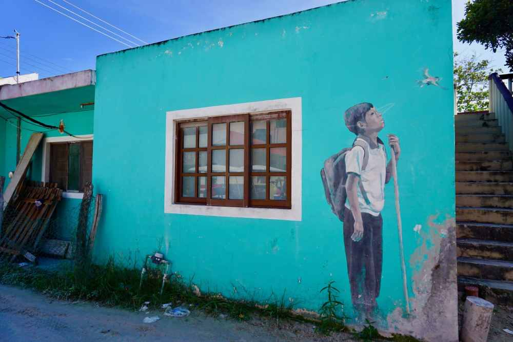Le street art de Holbox est très coloré. Cette fresque sur mur turquoise d'une jeune garçon à Isla Holbox, Mexique