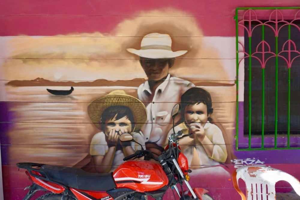 Street art d'un homme et ses enfants sur un mur rosé à Holbox, Mexique