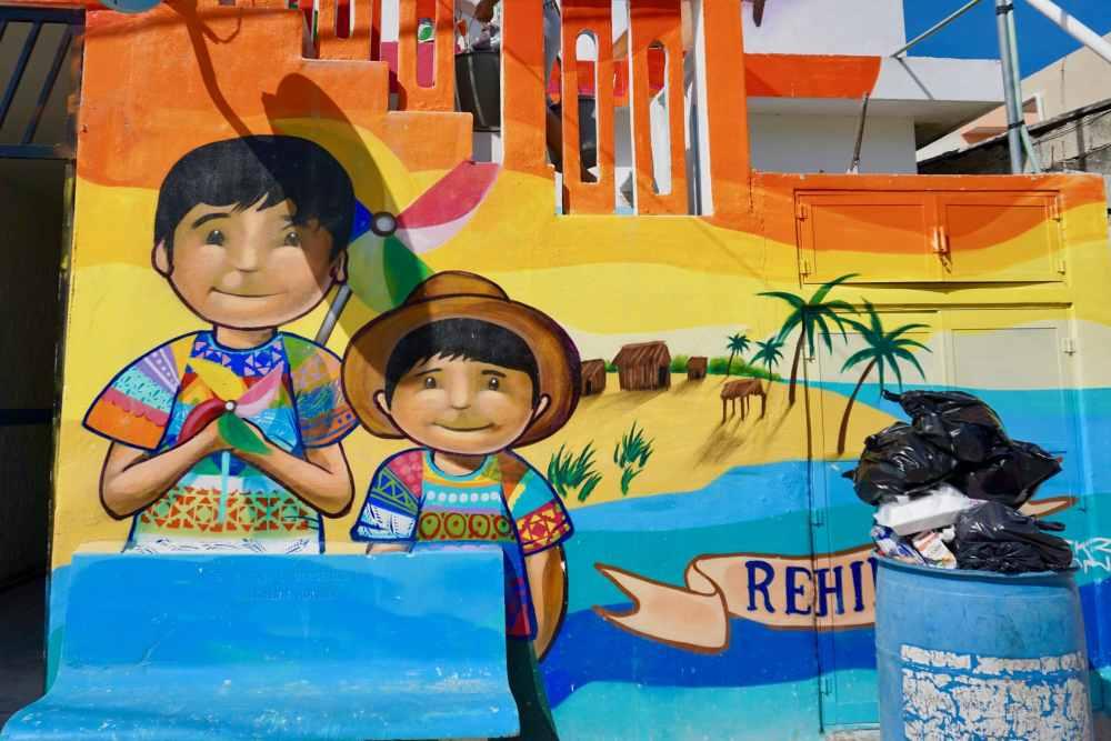 Fresque colorée à Holbox devant laquelle se trouve une poubelle pleine de vidanges