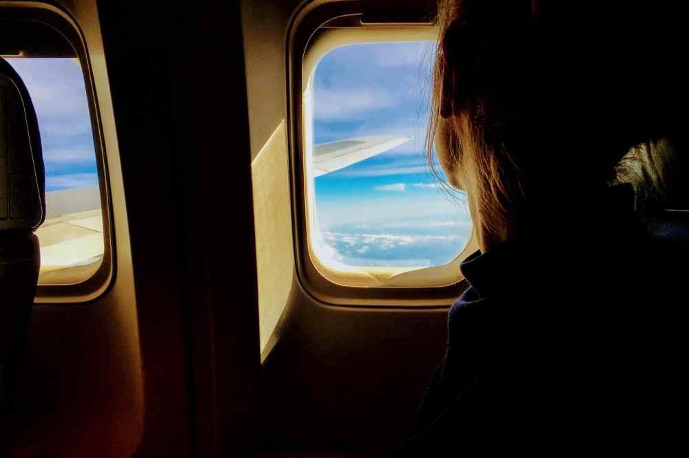 Une femme regarde par le hublot d'un avion