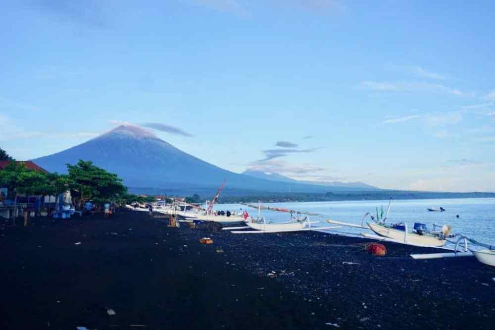 Lever de soleil sur la plage noire de Amed avec vue sur le Mont Agung à Bali