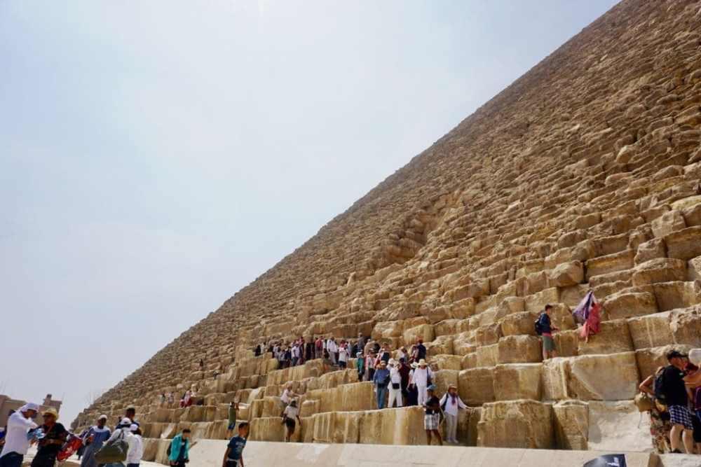 Plusieurs touristes font la queue devant l'entrée de la pyramide de Kheops