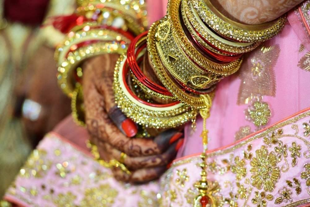 Les mains d'une Indienne à son mariage: bracelets, hennés, robe colorée