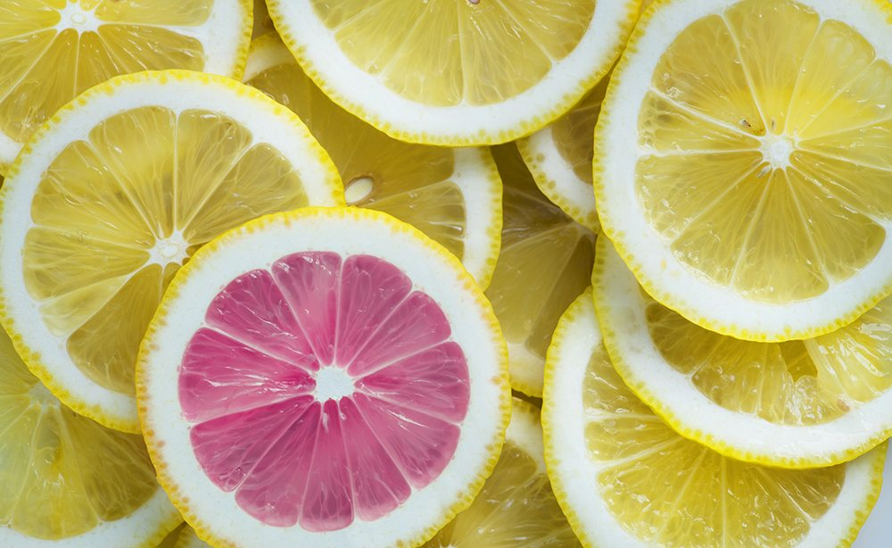 Closeup of slices of lemon and one pink slice standing out textured background