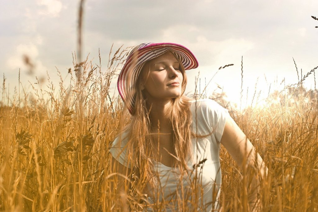girl closing her eyes in a field