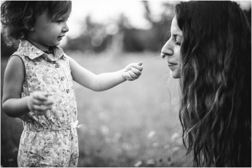 baby girl sharing flowers with mom during flower field session| jacksonville children photographer