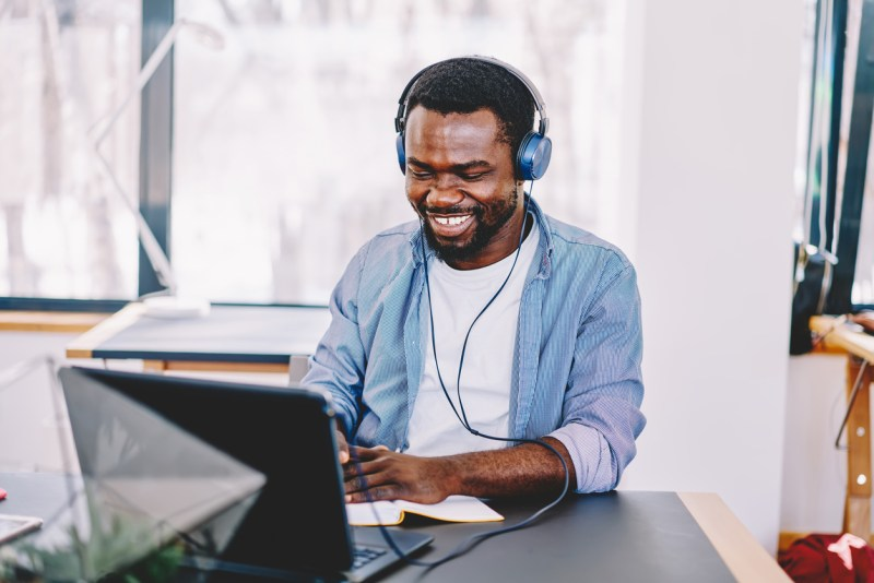 Man sitting in front of a laptop listening to music