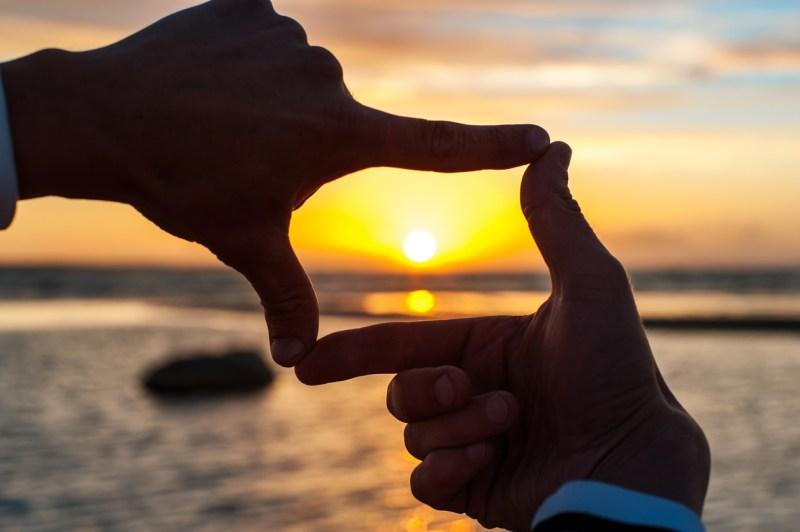 Composition finger frame- man's hands capture the sunset.